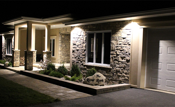 nightime picture of the front of a stone built house with lighting over the entrance porch/