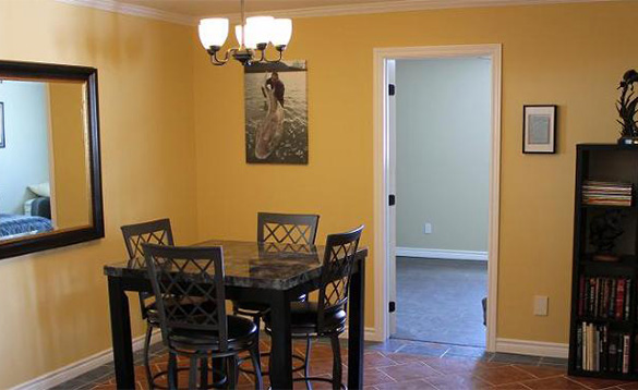 yellow painted room with a table and four chairs and books on a dark wooden book case/