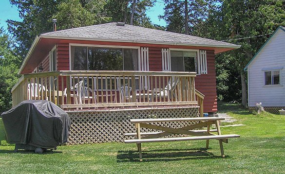 red painted wooden chalet with a veranda with tables and chairs on it/