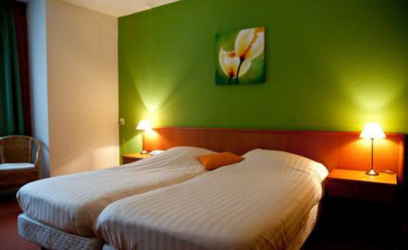 hotel bedroom with twin beds against a bright green wall with a picture of tulips in the middle of the wall/