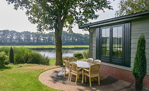 Table and six chairs on a paved patio area beside a chalet looking over to a lake at Arendshorst Resort, Holland/