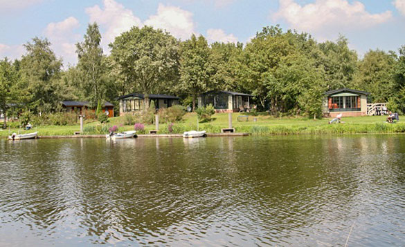 View across a lake to chalets amongst trees with rowing boats moored on the shoreline/