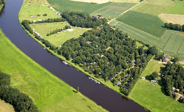 Aerial view of a canal and green fields in Holland/