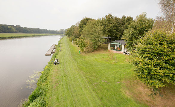 Angler fishing in a canal beside a chalet at Arendshorst Resort in Holland/