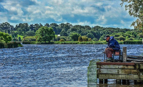 angler sitting on a wooden jetty fishing into a wide tree lined river on a sunny day/