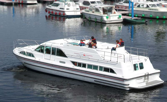 four people on a large white cruiser sailing past a marina with white cruisers moored in it/
