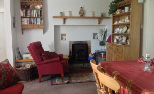Lounge at Lackaroe self-catering with chairs arranged around an open fire/