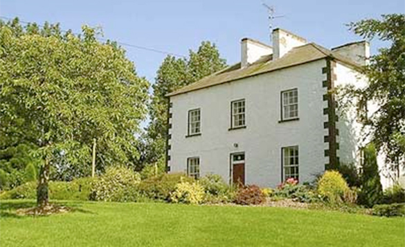 large white house with trees and lawn to the front/