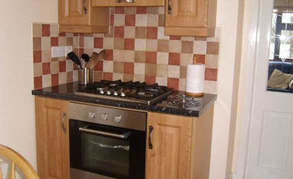 oven with gas hob and pine kitchen units and brown checkerboard tiles/