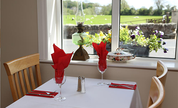 Dining table near a window with view over a stone wall to sheep grazing in a field/