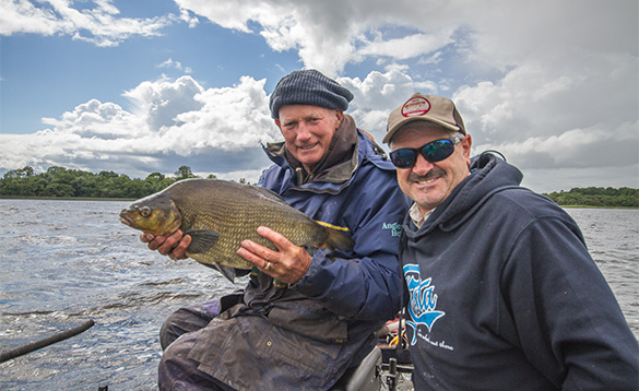 Two anglers at the edge of a lake in Co Cavan, one holding a bream/