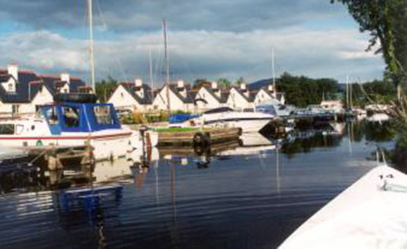 small marina with a number of cruising boats moored to jetties/