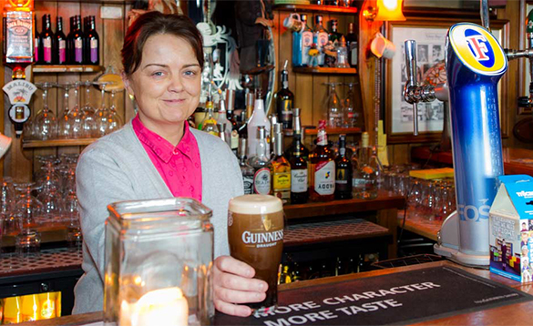 Lady serving a pint of Guinness in O'Callaghan's Bar, Coachford/