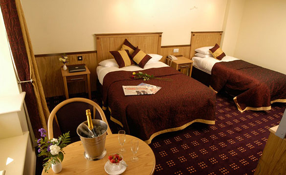 hotel bedroom with double and single bed with brown and gold bed linen and a small pine table with a bottle of champagne in a bucket with two glasses/