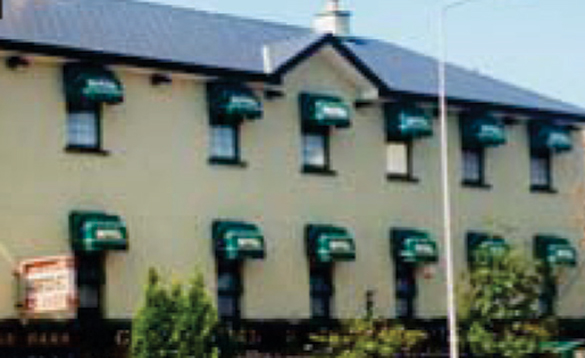 cream hotel with green canopies over each window/