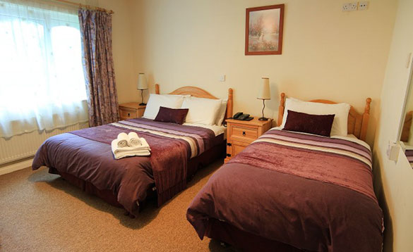 bedroom with single and double pine beds with mauve coloured bed linen /