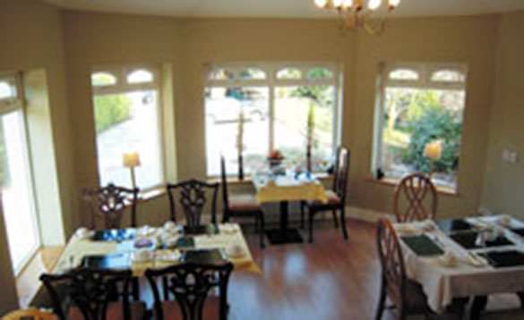 dining room with dark wooden tables and chairs, yellow tablecloths and set for breakfast/