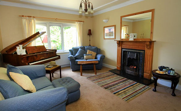 living room with grand piano in the corner and blue sofa and chairs/