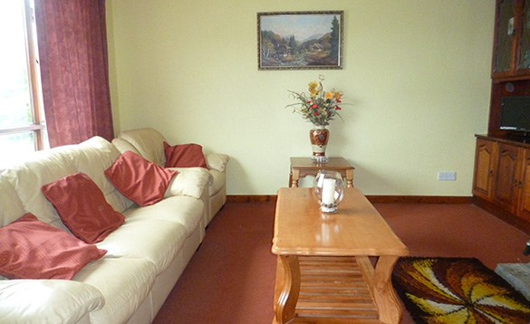 sitting room with large cream leather sofa and chair with deep pink cushions beside a light wood coffee table/