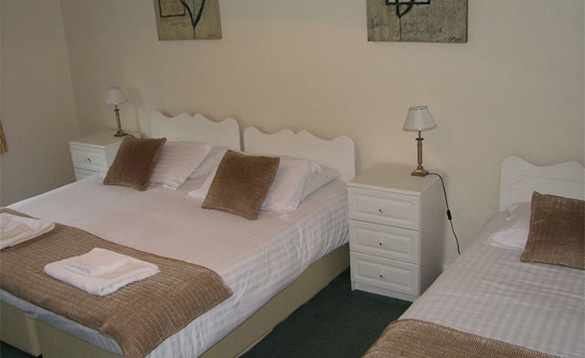 White painted bedroom with double and single bed with white bed linen and brown throws /