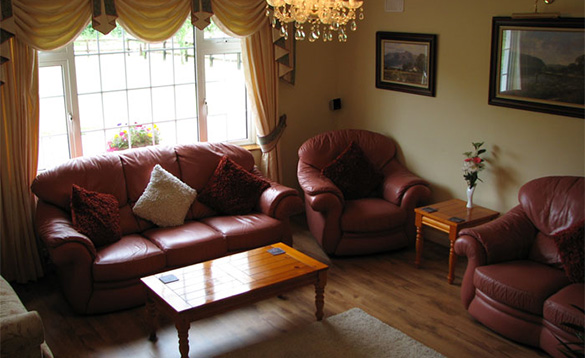 Living room with brown leather three piece suites around a coffee table/