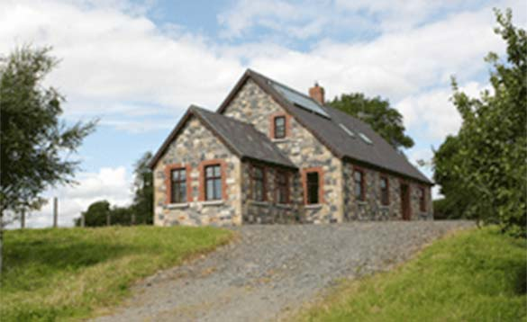 gravel driveway up a grass bank leading to single storey stone cottage/