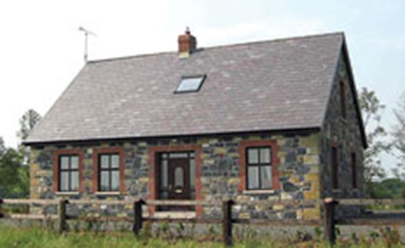 Single storey stone cottage with slate roof and wooden fence/