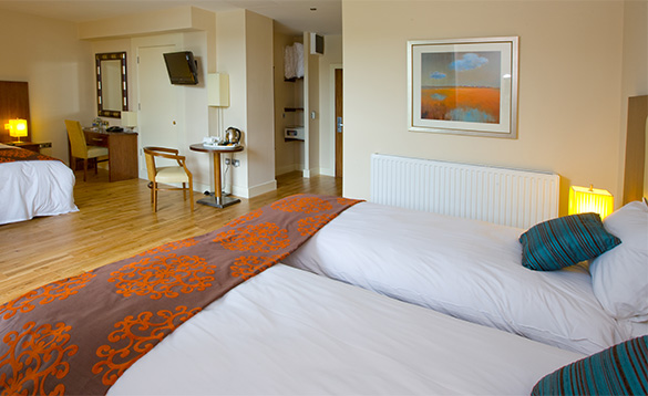 Hotel bedroom with three single beds with white bed linen and blue cushions/