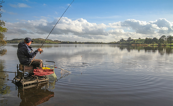 angler fishing whilst sitting on a tackle box stood in the water at the edge of a lake/