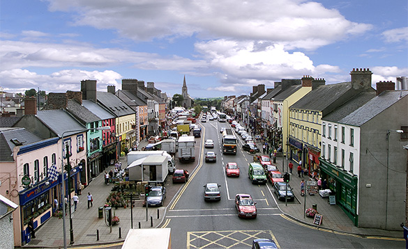 view down the main street of a busy town with cars parked either side of the road and brightly coloured buildings either side of the street/
