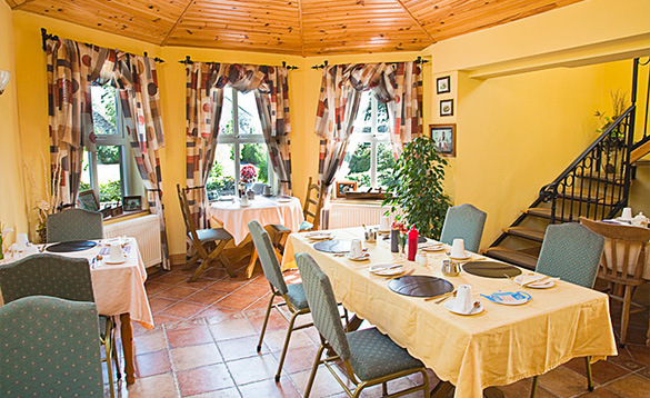 bright yellow painted dining room with tiled floor and a selection of table with yellow table cloths and chairs set for breakfast/