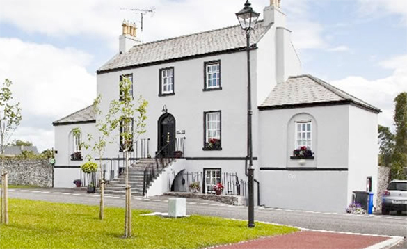 large three storey white painted house with steps leading up to the entrance /