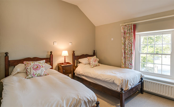 Bedroom with double and single bed in the Coach House on Belle Isle Estate/