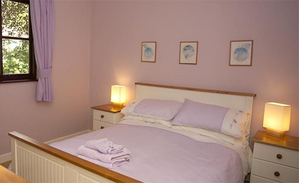 Lilac painted bedroom with white bed and bedside cabinets and lilac and white bed linen/