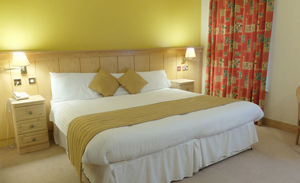 double bed against a yellow wall with white bed linen and gold cushions and throw/