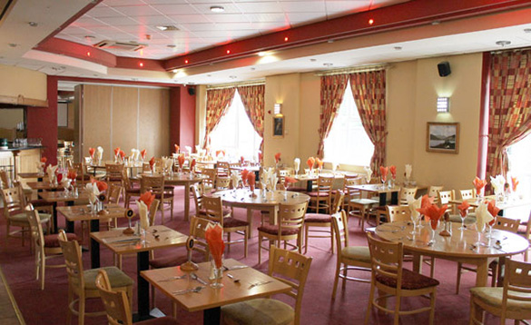 hotel restaurant with pink carpet and table set for dinner/