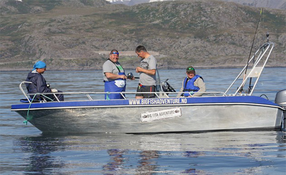 group of four anglers standing in a small fishing boat in a fjord/
