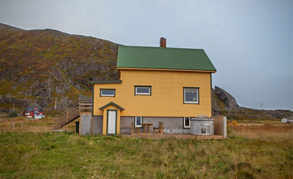 two storey building painted mustard yellow and green roof located beside a grassy hill/