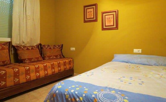 double bed in a room with mustard coloured walls and sofa beneath the window/