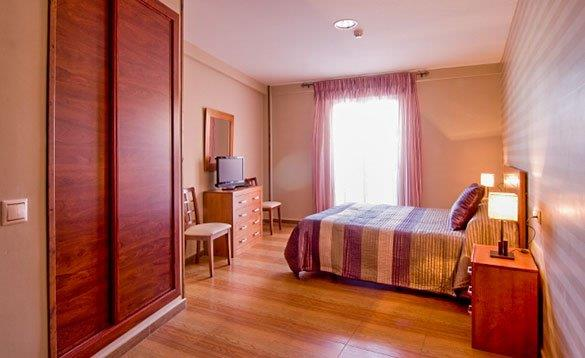 hotel bedroom with pine bedroom furniture and laminate flooring/