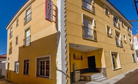 Three storey hotel painted a mustard colour situated on the corner of a street in Spain/