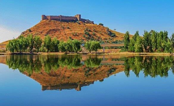 castle on top of a hill reflected in a lake/