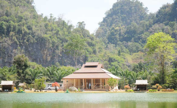 View across a lake in Thailand to a bungalow situated at the foot of tree covered hills/
