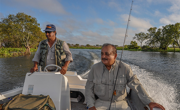 Two anglers on a speed boat travelling along a river in Corrientes, Argentina/