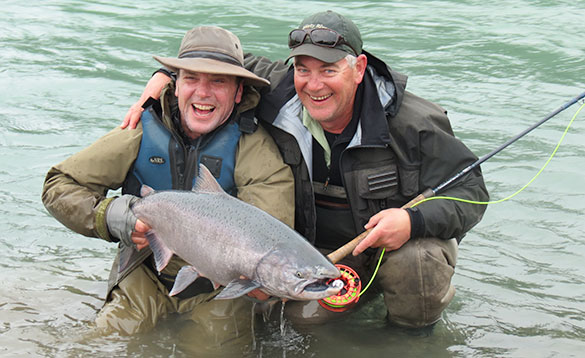 Two anglers holding a recently caught salmon in Canada/