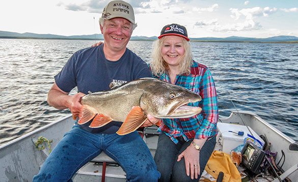 Lady sat on a boat next to an angler holding a Lake Char caught in the Yukon/