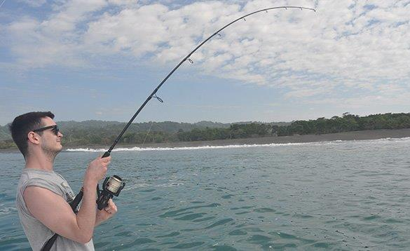 angler holding a bent over rod reeling in a fish/
