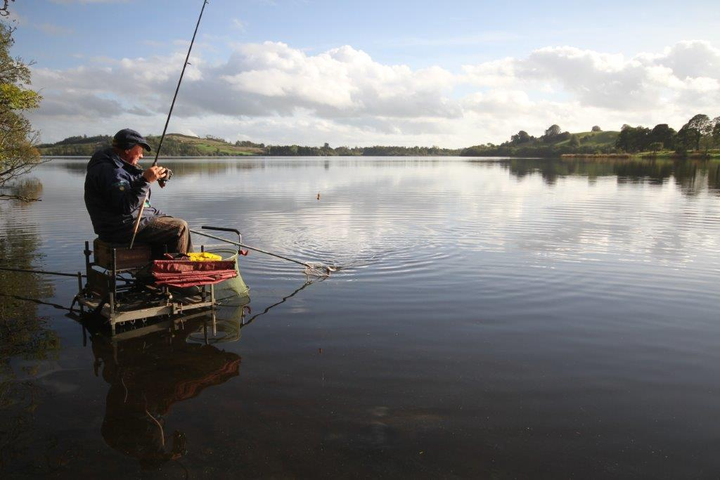 angler sitting on a tackle box in the shallows of a river fishing/