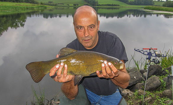 angler knelt at the edge of a river holding a tench/
