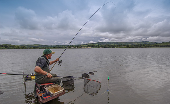 angler sitting on a tackle box in the shallow waters at the edge of a river fishing/
